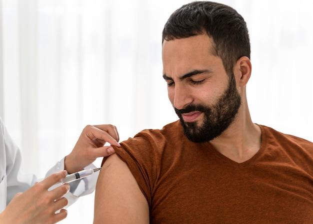 Médecin vue de face vaccinant un homme barbu