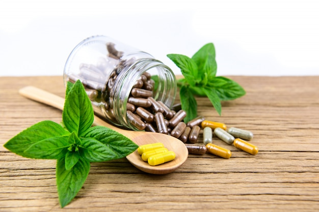 Médecine alternative à base de plantes en capsules sur une table en bois