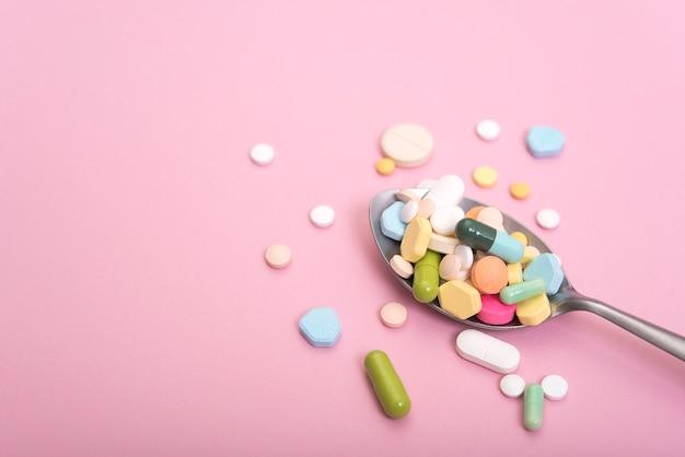 Médecine colorée en cuillère. pharmacie sur fond rose.