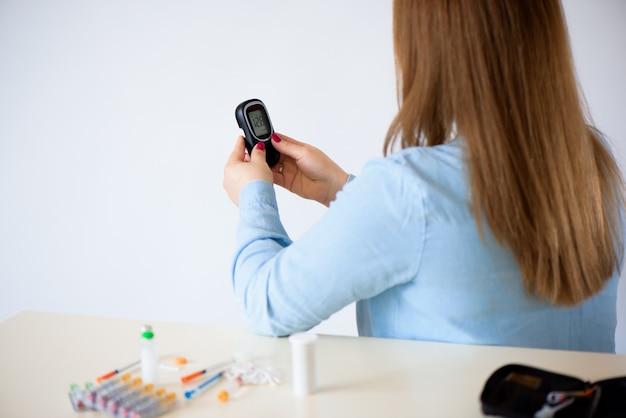 Médecine, diabète, glycémie, soins de santé et concept de personnes - gros plan de femme vérifiant le niveau de sucre dans le sang par glucomètre à la maison