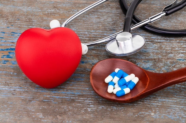 Médecine pilules, comprimés et gélules sur cuillère en bois avec cœur.