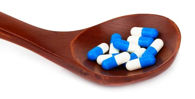 Médecine pilules, comprimés et gélules sur cuillère en bois isolé sur blanc.