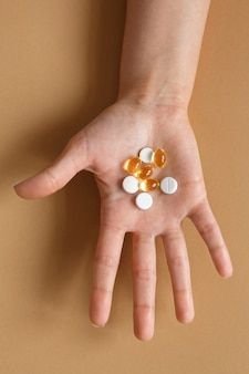 Médecine et soins de santé. pilules et capsules avec des vitamines dans la paume d'une main féminine. régime alimentaire et alimentation saine