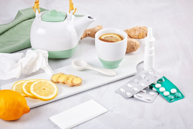 Médecine traditionnelle et méthodes alternatives de guérison de la grippe. pilules, vaporisateur nasal et thé chaud au citron et au gingembre