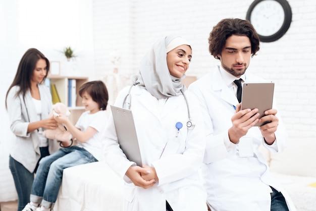 Les médecins arabes regardent quelque chose sur la tablette.