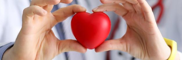 Les médecins cardiologues tiennent coeur jouet rouge en clinique