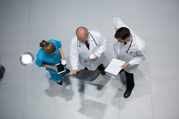 Médecins et chirurgiens discutant des rayons x tout en prenant un café