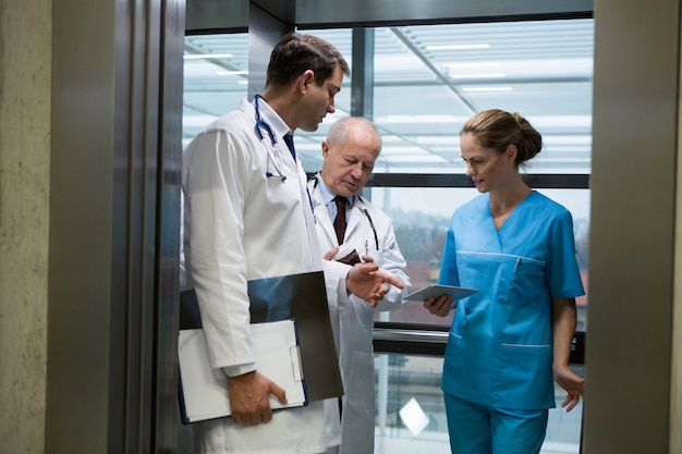 Médecins et chirurgiens utilisant une tablette numérique dans l'ascenseur