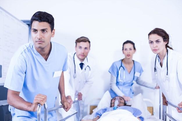 Médecins concernés debout près du patient sur son lit à l'hôpital