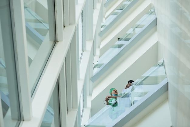 Médecins debout sur le balcon de la clinique et discutant des cas difficiles, des symptômes et du traitement