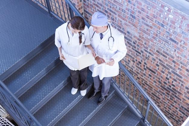 Médecins debout dans l'escalier et vérifiant un rapport médical à l'hôpital