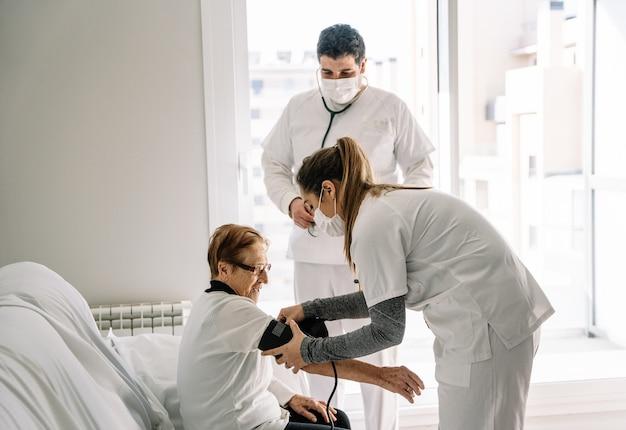 Médecins diagnostiquant la pression artérielle d'une femme âgée