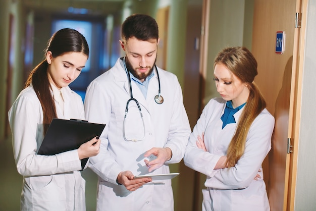 Médecins discutant du cardiogramme du patient sur la tablette.