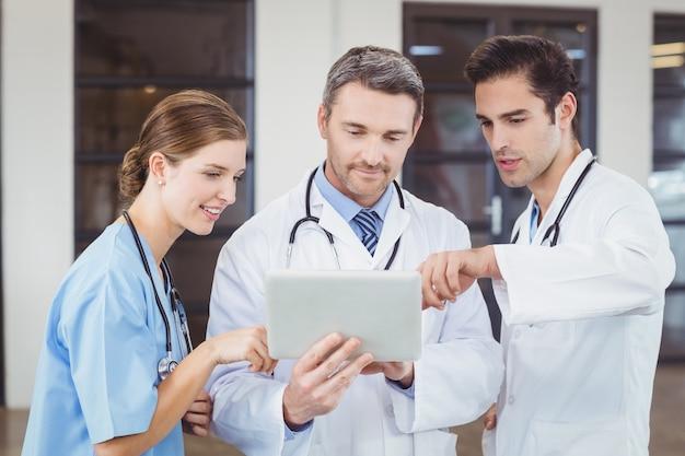 Médecins discutant tout en tenant une tablette numérique