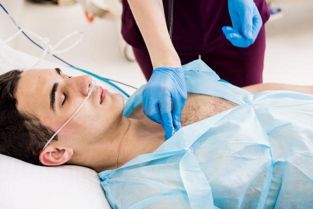 Les médecins donnent la réanimation à un patient de sexe masculin dans la salle d'urgence. massage cardiaque
