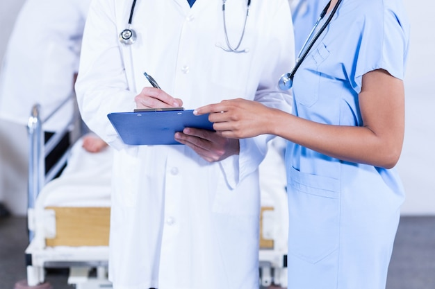 Médecins écrivant sur le presse-papiers à l'hôpital
