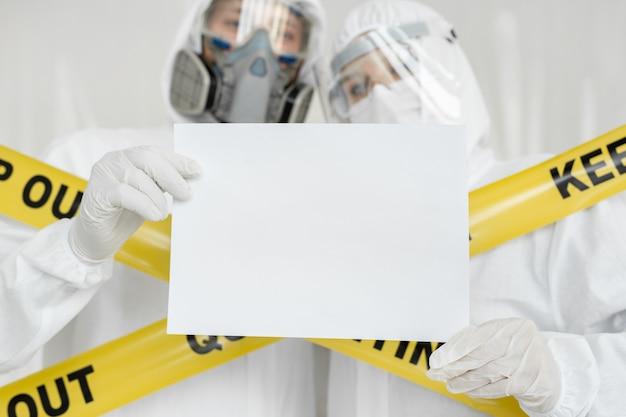 Médecins épidémiologistes homme et femme tiennent un tableau blanc vide blanc avec place pour l'image de texte. ligne jaune keep out quarantine