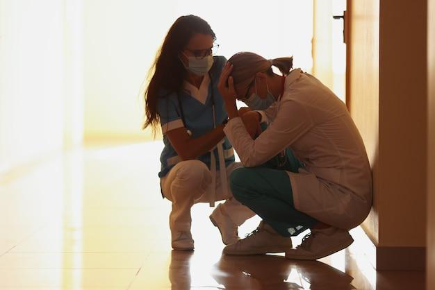 Médecins fatigués en masque médical de protection assis sur le couloir
