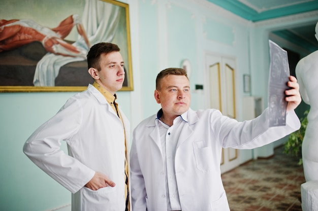 Des médecins habiles examinent une image aux rayons x de la partie du corps de leur patient à l'hôpital.
