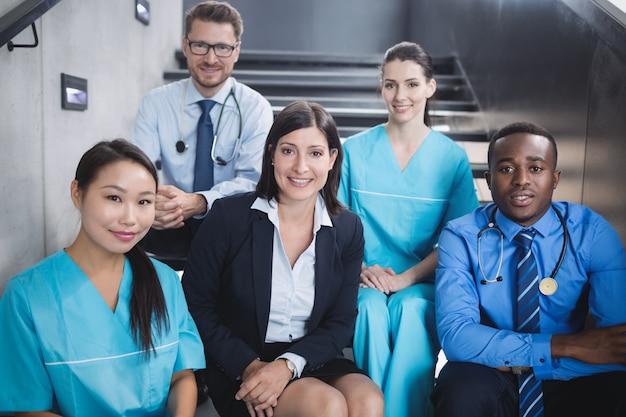 Médecins et infirmières assis sur l'escalier