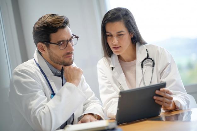 Médecins masculins et féminins examinant les résultats des patients