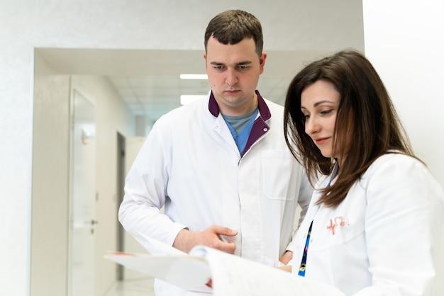 Médecins masculins et féminins parlant et regardant les papiers en clinique. homme et femme, médecins discutant à l'hôpital. médecin et infirmière discutant de la maladie. docs et assistant conversation