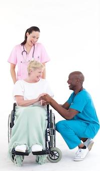 Médecins avec un patient dans une chaise roulante