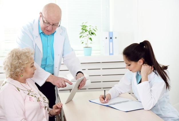 Médecins et patient heureux dans la clinique de l'hôpital