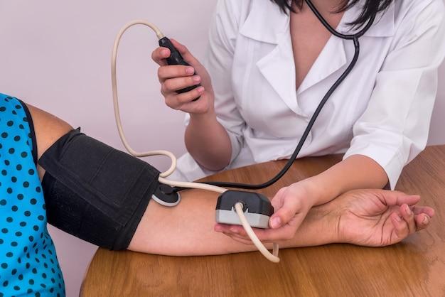 Médecins et patients mains avec tonomètre mesurant la pression artérielle