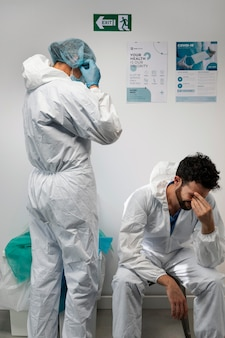 Médecins à plan moyen portant une combinaison de protection