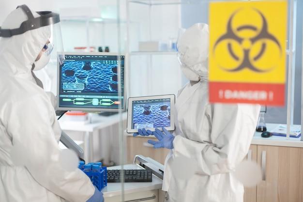 Médecins portant une combinaison de protection individuelle travaillant dans une zone de danger de laboratoire à l'aide d'un tablet pc