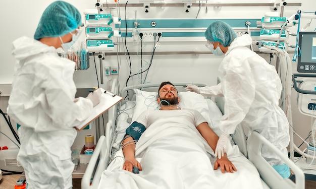 Les médecins portant des combinaisons de protection et des masques surveillent l'état du patient