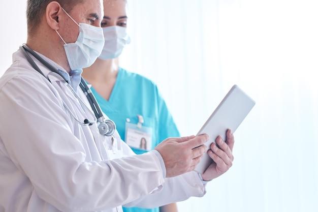 Des médecins portant des masques faciaux consultent des données en ligne sur une tablette numérique tout en discutant des résultats des tests de coronavirus