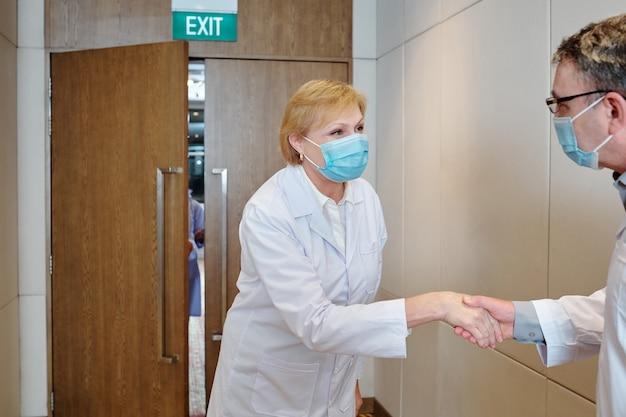 Médecins positifs portant des masques médicaux se serrant la main et échangeant leurs opinions après une grande conférence