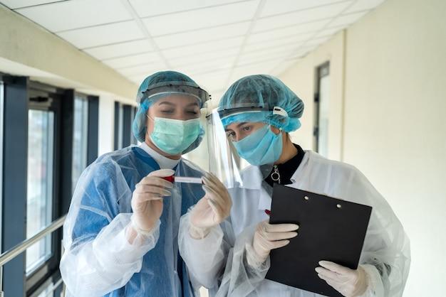 Médecins à la recherche d'un tube à essai avec du sang avec un rezult positif au coronavirus.