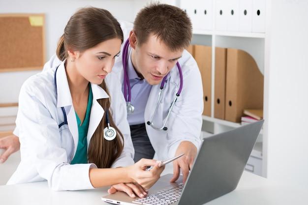 Médecins regardant un moniteur d'ordinateur portable
