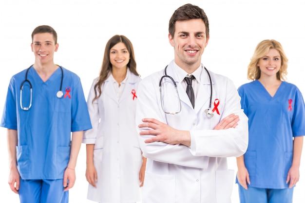 Des médecins avec un ruban rouge soutiennent une campagne de sensibilisation au sida.