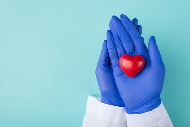 Des médecins sauvent des vies pendant le concept d'épidémie de coronavirus. haut au-dessus de la vue aérienne photo du médecin en gants tenant un coeur rouge isolé sur fond bleu turquoise