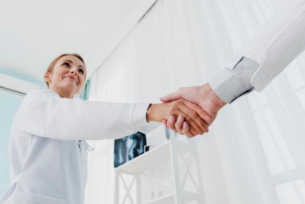 Médecins se serrant la main à angle faible