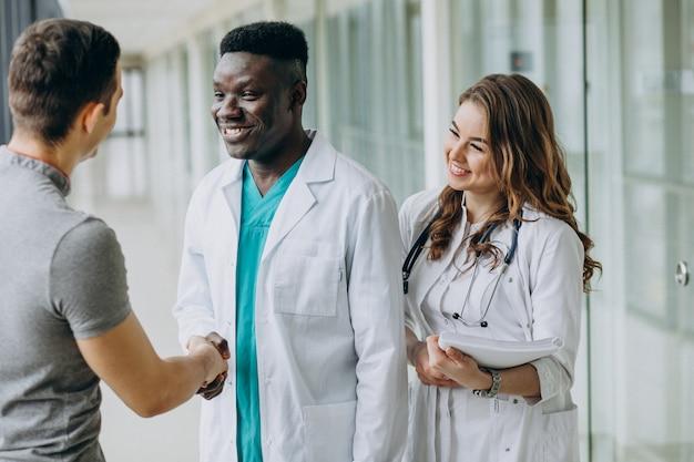 Médecins serrant la main du patient, debout dans le couloir de l'hôpital