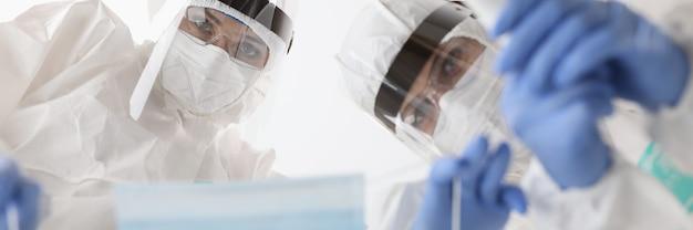 Médecins en tenue de protection mettant un masque sur le patient et mesurant la température