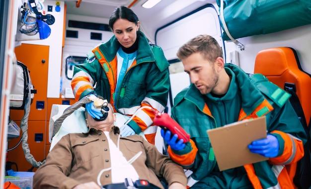 Les médecins d'urgence ou les ambulanciers travaillent avec un patient âgé alors qu'il se trouve sur une civière dans une ambulance.