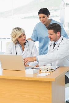 Médecins utilisant un ordinateur portable ensemble au cabinet médical