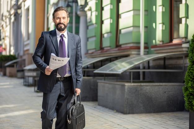 Médias imprimés. bel homme d'affaires positif marchant au travail tout en tenant un journal quotidien