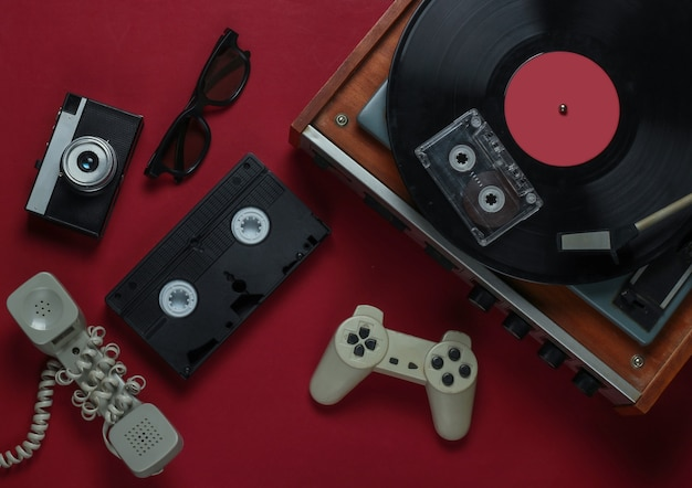 Médias rétro et divertissement à plat. tourne-disque vinyle avec disque vinyle, appareil photo, cassette vidéo, cassette audio, manette de jeu, combiné sur fond rouge. années 80. vue de dessus