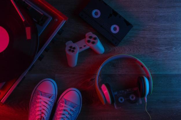 Médias rétro et trucs à l'ancienne sur un plancher en bois avec néon rouge-bleu