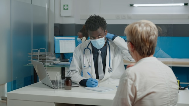 Medic avec blouse blanche assis au bureau tout en parlant à une femme plus âgée