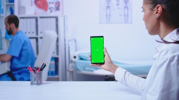 Medic en blouse blanche tenant un smartphone avec écran vert dans une armoire d'hôpital. infirmière portant un uniforme bleu médical.