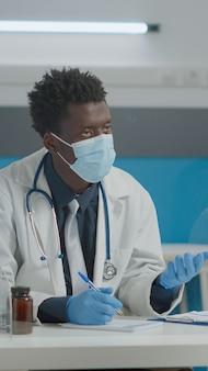 Medic consultant un patient âgé avec un masque facial et des gants