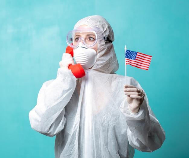 Medic dans des vêtements de protection tenir le combiné 911 rouge et le drapeau américain